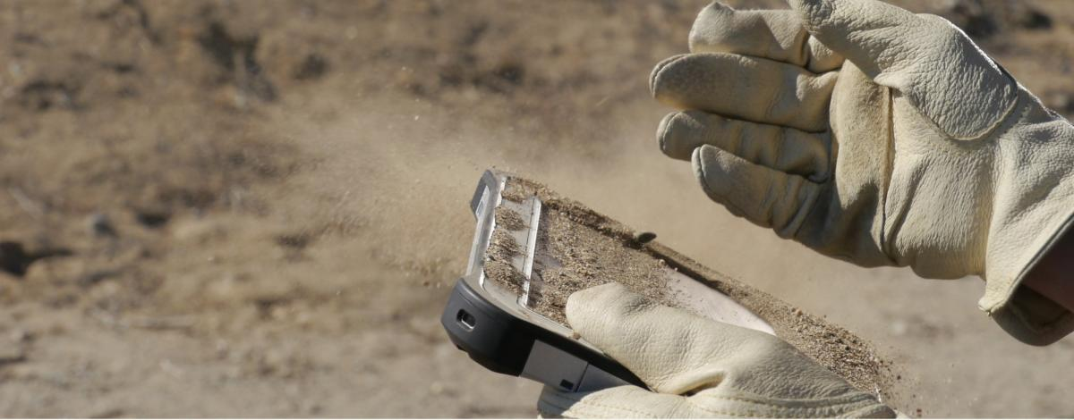 A TOUGHBOOK G1 being used in a dirty environment with gloved hands
